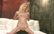 Small boobed blonde sits on an orgasm toy